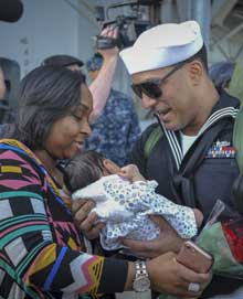 SAN DIEGO (Feb. 2, 2018) Operations Specialist 2nd Class Jesse Soto holds his newborn child for the first time during the homecoming of the amphibious assault ship USS America (LHA 6). America, part of the America Amphibious Ready Group, with embarked 15th Marine Expeditionary Unit (MEU), is returning from a regularly scheduled deployment to the Western Pacific and Middle East. The U.S. Navy has patrolled the Indo-Pacific region routinely for more than 70 years promoting peace and security. U.S. Navy Photo by MC2 Jesse Monford