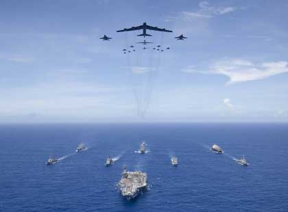 PHILIPPINE SEA (Sept. 17, 2018) The aircraft carrier USS Ronald Reagan (CVN 76) leads a formation of Carrier Strike Group (CSG) 5 ships as U.S. Air Force B-52 Stratofortress aircraft and U.S. Navy F/A-18 Hornets pass overhead for a photo exercise during Valiant Shield 2018. The biennial, U.S. only, field-training exercise focuses on integration of joint training among the U.S. Navy, Air Force and Marine Corps. This is the seventh exercise in the Valiant Shield series that began in 2006. U.S. Navy photo by MC3 Erwin Miciano